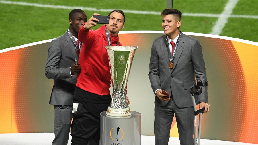 Zlatan Ibrahimovic taking photo with Europa League trophy